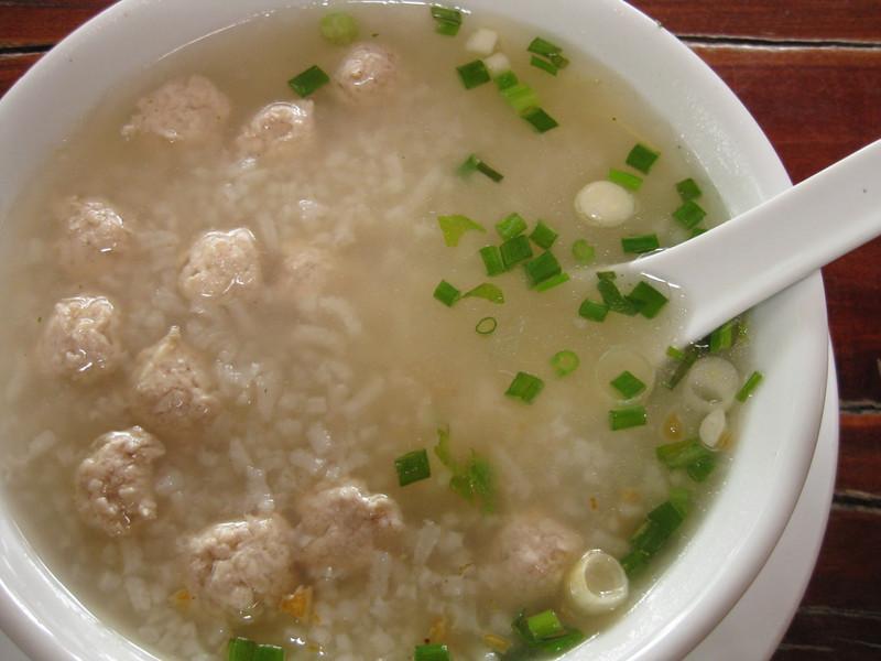 Thai breakfast: chicken balls, rice, soup and koriander