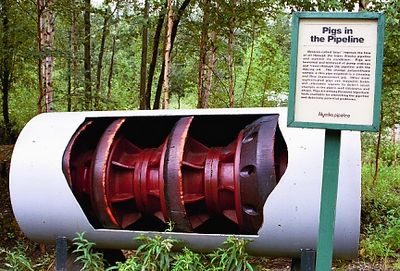 "A pipeline ""pig"" (shown in cut away) which was used to clean the inside of the pipe. Called a pig because of the squealing noise it makes when sent between pumping stations."