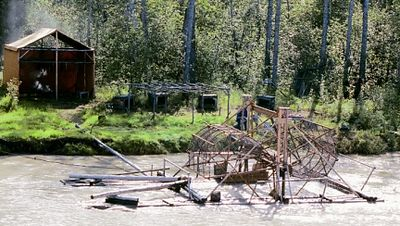 A salmon wheel, used to catch salmon as they swim upstream along the river's edge. The wheel turns with the current and scoops the salmon into a cage.