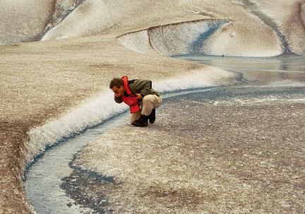 Rick takes a drink of cold, flowing glacier melt.