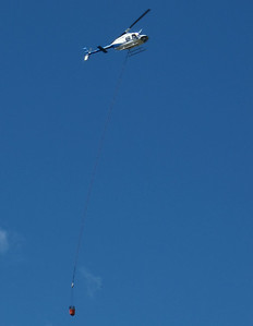 Heilcopter bringing a bucket of water to drop on a fire.