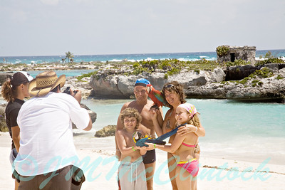 A resort photographer with his pet birds.  He is wandering the beach photographing the families with his birds.  I have no idea who this family is, but they look great with birds.