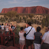 A crowd gathers to see the sun come up on Uluru.