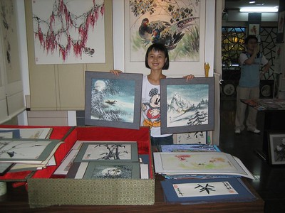 This student (Wang Li) from an art school in Xian invited me to come see the work of her school. She is holding up works by her teacher (Li Qing). The mountain scene on the right looks like her home area, she said.   (I had to buy one in order to get her permission for this photo, so she's a skilled salesperson, too. I bought the smaller bamboo one in foreground.)