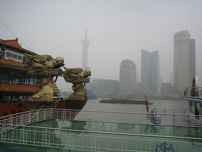 Cruise boat with dragon heads; barge carrying logs on Huangpu River; buildings across the river are in the Pudong New Area, which is growing rapidly.