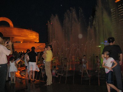 People enjoying the fountain in People's Square on a moonlit night.  Kids ran in and out, laughing. Other people were flying kites high above the fountain.  Building at left is the Shanghai Museum.