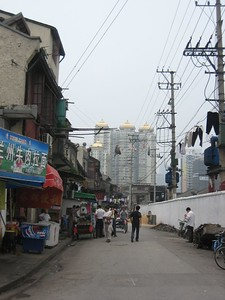 Contrast of old and new along Shanghai streets. Gleaming gold roofs in distance beyond bras and other laundry hanging on utiltiy wires across  the road.