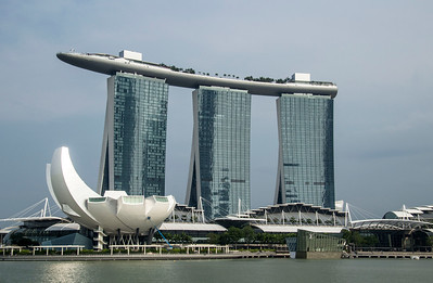 """Singapore Marina Bay Sands  resort features a 2,561-room hotel, a 1,300,000-square-foot (120,000 m2) convention-exhibition center, the 800,000-square-foot (74,000 m2) The Shoppes at Marina Bay Sands mall, a museum, two large theatres, seven """"celebrity chef"""" restaurants, two floating Crystal Pavilions, an ice skating rink, and the world's largest atrium casino with 500 tables and 1,600 slot machines."""