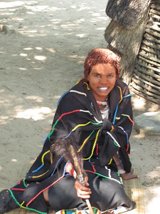 This is a Zulu fortune teller who paints her face and hair with red clay.