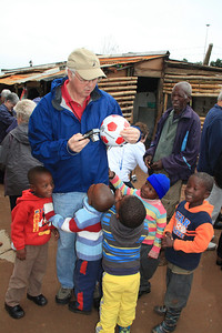 Ginny and Mary had bought a soccer ball for the kids at an earlier stop.  Rick was swarmed by the kids when they saw the ball.
