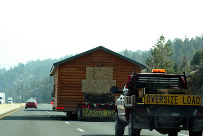 A log cabin was driving down the road. We caught up to it and was able to pass the cabin safely.