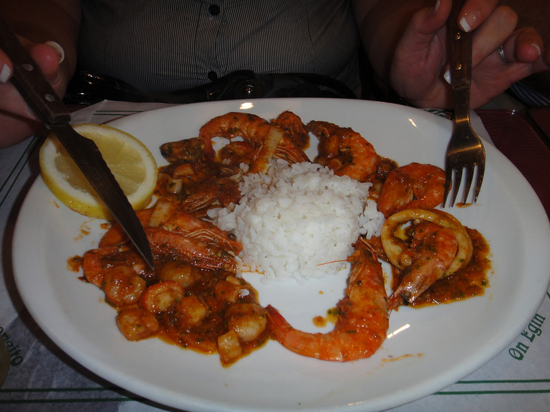 Mary eating seafood with a spicy red sauce