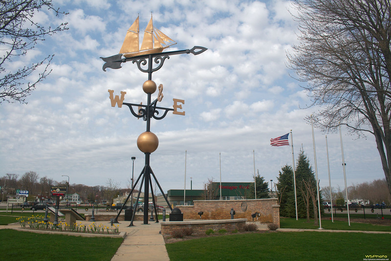 """White Lake Weather Vane<br /> Montague, MI<br /> <br /> Standing on the corner of Dowling and Water Street, the hand forged aluminum weather-vane is 48 feet high, 14 feet long, and weighs 4,300 pounds. This operating weathervane has  a working weather station in its base with foot access available.<br /> <br /> The ship on top of the weathervane is the Ella Ellenwood, a Great Lakes lumber schooner whose home port was White Lake, off Lake Michigan, in Montague. In October of 1901, the Ellenwood ran aground with a full load eight miles north of Milwaukee. The crew abandoned ship, and the wind and waves of a fall storm broke the ship to pieces. The next spring, a portion of the ship's nameplate, bearing the word """"Ellenwood,"""" was found in White Lake. Almost miraculously, the nameplate had drifted back east across Lake Michigan to the ship's home port!  The nameplate is still exhibited in the Montague City Hall."""