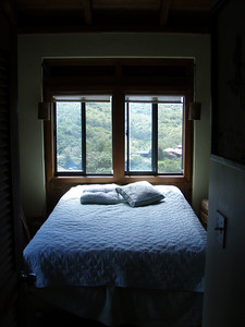View of the bedroom.  Amazing cross breezes through the windows all night long.  The roosters down the hill will wake you up at first, but eventually you don't hear 'em anymore.