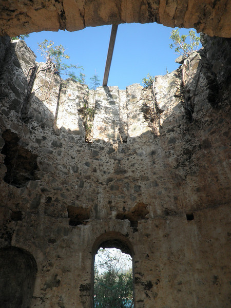 Looking up the inside of the ruins of an old windmill used to process sugarcane.  The jagged hole on the middle left is where the hive lives.  The hole above the left side of the door had a huge rosary in it.  The right side of the door hole is waiting for a random treasure...