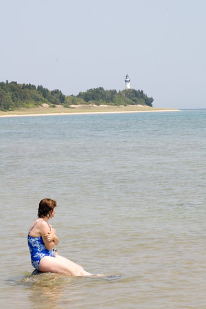 Enjoying the beach to ourselves on South Manitou Island (in Lake Michigan.)  Ruth rests on a rock.  The island's lighthouse in the distance.
