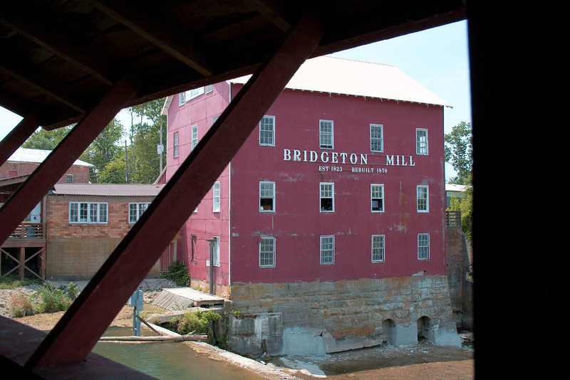 "Bridgeton Mill & Covered Bridge<br /> <br /> The Bridgeton Covered Bridge crosses over the Bridgeton Mill pond which is created by the mill dam. The covered bridge being over a waterfall makes it ""Indiana's Most Famous Covered Bridge."" The bridge was original built in 1868, closed to traffic in 1968, tragically burned down in 2005 and then rebuilt in 2006.<br /> <br /> During our visit the sun was high over head (not the best for photos), it was still opressively hot (over 100 degrees) and we were in the middle of a drought so waterfall wasn't as impressive as it normally would be. Still, the site and its features were impressive. I hope to return sometime in the future to shoot some better photos at a time when weather and lighting conditions are better. I'm actually wanting and hoping to do a bridge tour of all of Parke county (there's something like 33 covered bridges in the county) to enjoy capturing photos of and documenting them all.<br /> <br /> The Bridgeton Mill was established in 1823 and rebuilt in 1870. It is the oldest continually operating mill in Indiana (Possibly the Midwest ). It's claim to fame is having been open every year for over 180 years. The waters of the Big Raccoon Creek power this historic mill which sits next to Indiana's Most Famous Covered Bridge.<br /> <br /> For more information about the mill and bridge please visit the web links included below.<br /> <br />  <a href=""http://bridgetonmill.com/"">http://bridgetonmill.com/</a><br />  <a href=""http://goo.gl/maps/bS2a"">http://goo.gl/maps/bS2a</a>"