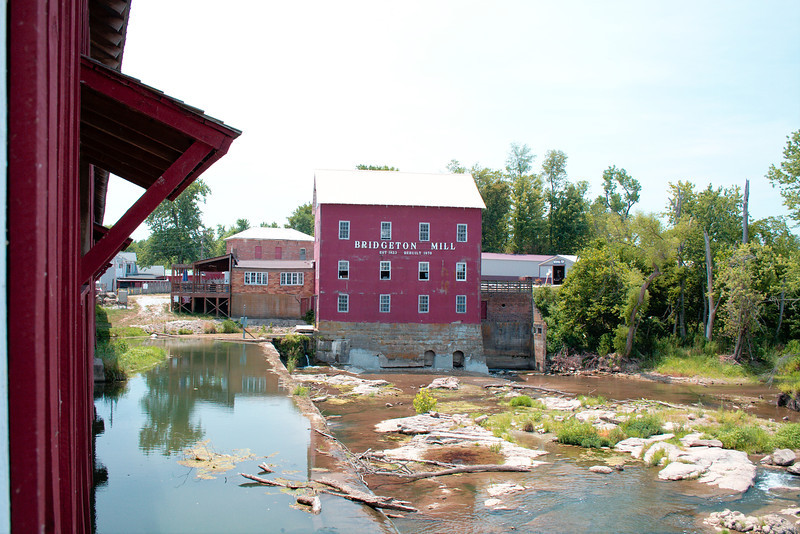 """Bridgeton Mill & Covered Bridge<br /> <br /> The Bridgeton Covered Bridge crosses over the Bridgeton Mill pond which is created by the mill dam. The covered bridge being over a waterfall makes it """"Indiana's Most Famous Covered Bridge."""" The bridge was original built in 1868, closed to traffic in 1968, tragically burned down in 2005 and then rebuilt in 2006.<br /> <br /> During our visit the sun was high over head (not the best for photos), it was still opressively hot (over 100 degrees) and we were in the middle of a drought so waterfall wasn't as impressive as it normally would be. Still, the site and its features were impressive. I hope to return sometime in the future to shoot some better photos at a time when weather and lighting conditions are better. I'm actually wanting and hoping to do a bridge tour of all of Parke county (there's something like 33 covered bridges in the county) to enjoy capturing photos of and documenting them all.<br /> <br /> The Bridgeton Mill was established in 1823 and rebuilt in 1870. It is the oldest continually operating mill in Indiana (Possibly the Midwest ). It's claim to fame is having been open every year for over 180 years. The waters of the Big Raccoon Creek power this historic mill which sits next to Indiana's Most Famous Covered Bridge.<br /> <br /> For more information about the mill and bridge please visit the web links included below.<br /> <br />  <a href=""""http://bridgetonmill.com/"""">http://bridgetonmill.com/</a><br />  <a href=""""http://goo.gl/maps/bS2a"""">http://goo.gl/maps/bS2a</a>"""