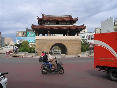The East Gate in downtown Hsinchu with one of the ever-present scooters.  Scooter drivers have no fear at all, and can be seen zipping against traffic, across traffic, through traffic, and in some cases even with traffic.  Sometimes its just one person, but some of the more memorable combinations are: Mother on back, father driving up front, one-year old baby in between...  The popular guy driving, girl sitting side-saddle behind (just about lose her knees that way, considering how close scooters and cars come together.)  Mother with two small children standing in front.  And best of all was two young women, driver in front, girl in back somehow holding on to the driver, but very obviously completely asleep!