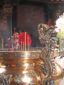Giant brass kettle guarded by dragons with burning incense-stick offerings.