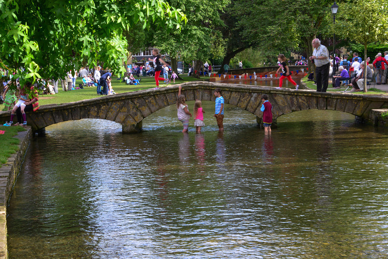Kids playing in the water (fridged) in Burton on the Water.