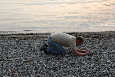 Ok he is either praying or taking a close up shot of pebbles.
