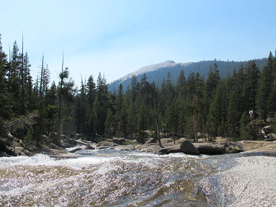 A branch of the Tuolumne River flows down through the camp
