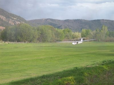 A glider coming in for a landing at Durango Gliderport next to the RR tracks.