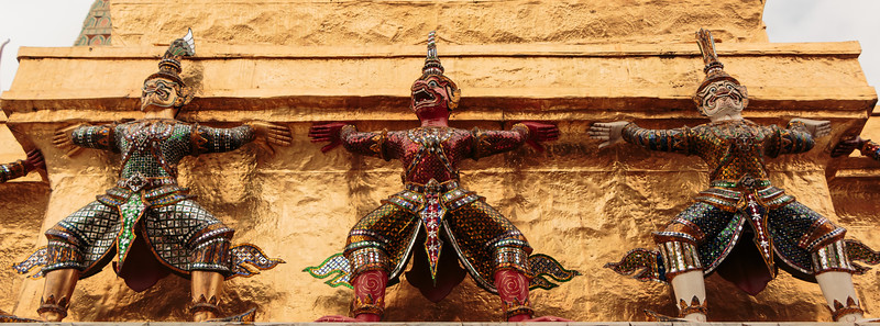 Ancient guards hang off the side of Buddhas Temple