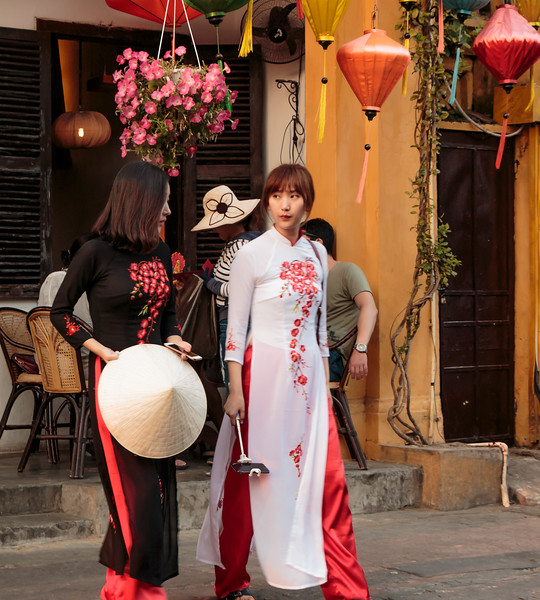 Two stylish women coming out of a shop and it appeared that all of the tourists (which were mainly Chinese) carried some type of smart phone