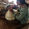 This young woman  was making the straw hat seen in the picture