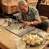 This craftsmen is arranging shell fragments to create his portrait