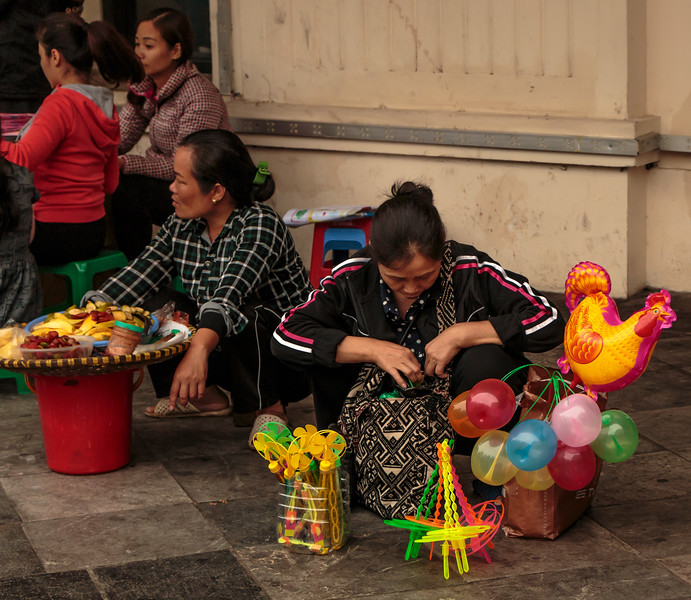 A couple of women on a street corner with their wares for sale. One of them was selling toys and the other some sort of food