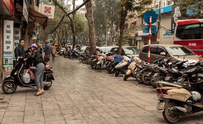 Street scene in downtown Hanoi, lots of motorcycles and scooters parked mostly on the sidewalks