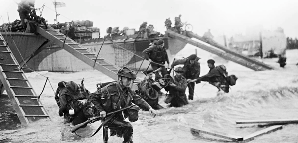 June 1944: Royal Marine Commandos of Headquarters, 4th Special Service Brigade, make their way from LCI(S) (Landing Craft Infantry Small) onto 'Nan Red' Beach at Saint-Aubin-sur-Mer. 6 May 2014: A view of the sea in the Juno beach area today. Photographs by Lt Handford/IWM/Getty and Peter Macdiarmid/Getty