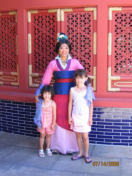 Heather and Evelyn posing with Mulan.<br /> <br /> This picture is taken outside the movie theater at the Chinese pavilion in Epcot.
