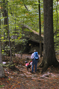 Albany NH - Boulder Loop Trail  Judy and her hounds ponder the hanging boulder.