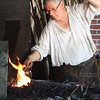 A Williamsburg blacksmith (not a reenactor) reheats a piece he is working on to the delight of the onlookers.<br /> DW5D4137
