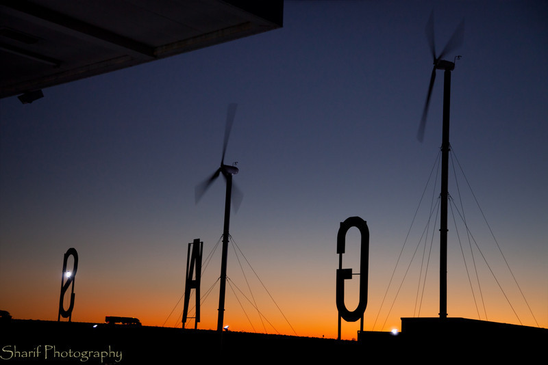 A gas station with windmills provides a contrast between renewable and fossil energy.