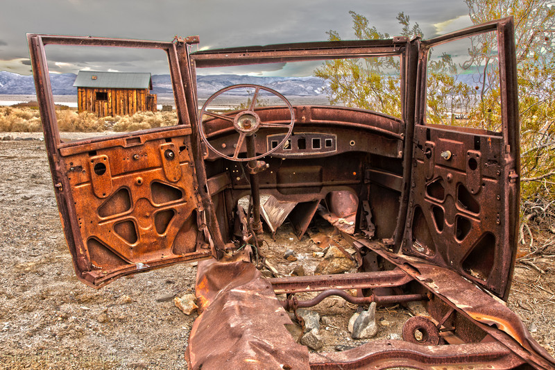 The rusted remains of what once was a car looks out over the valley in the ghost town of Ballarat, California.