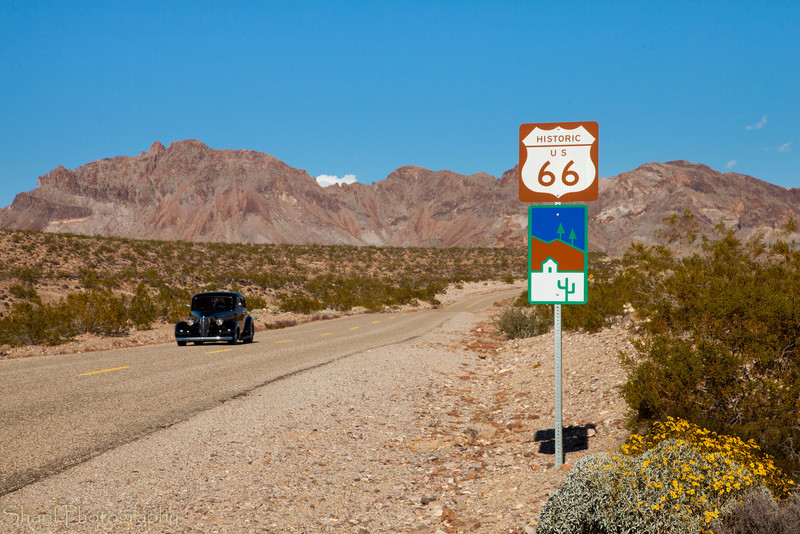 A vintage car drives on a restored stretch of route 66 near a sign.