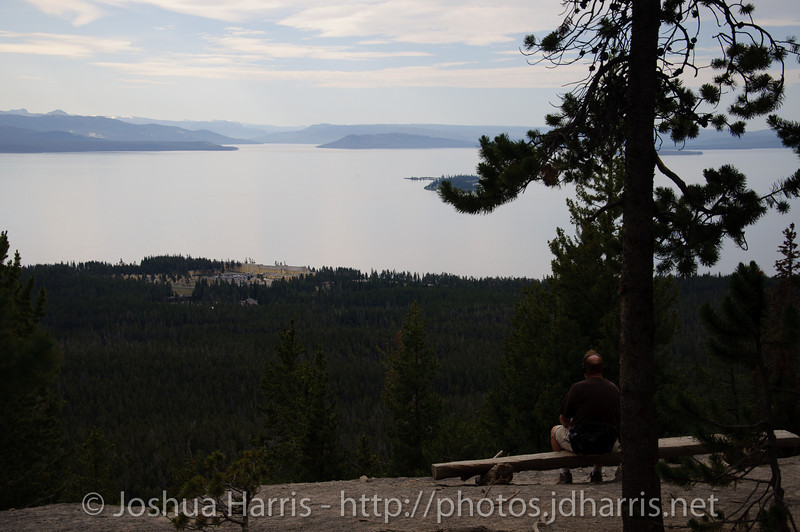 A man watching the sun rise over Yellowstone Lake from the top of the Elephant Back trail