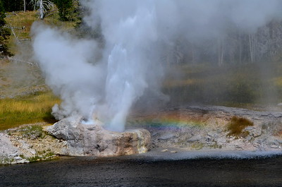 Rainbow is visible in the spray.
