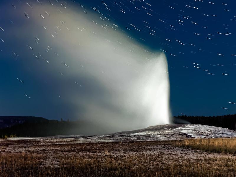Old Faithful geyser at night