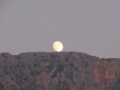 Moon sitting on the edge of the mountain