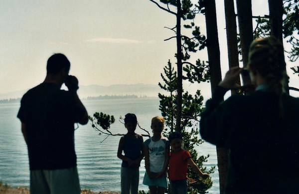 My son on video camera, wife on still camera, and their three girls, early morning with the fog still over Yellowstone Lake.