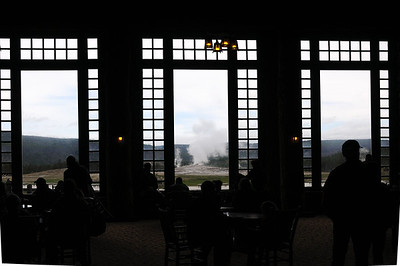 Old Faithful  seen through the window of Old Faithful Inn