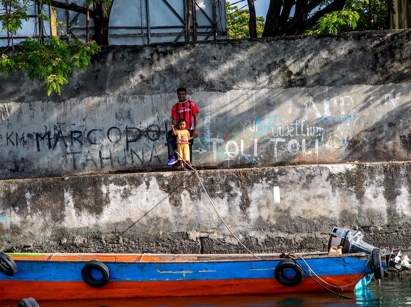 A child waving in the Manado, Indonesia harbor