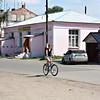 Girl riding her bike in front of the main grocery store in Vyatskoe.