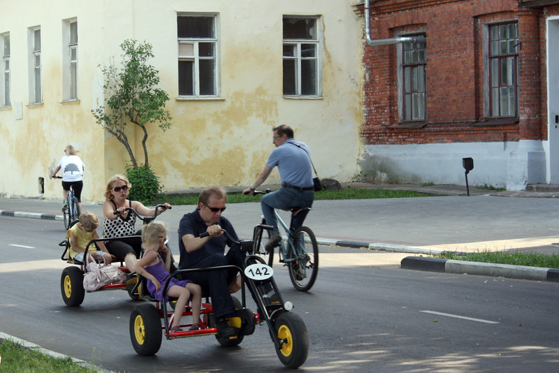 A mom & dad pedaling their kids.